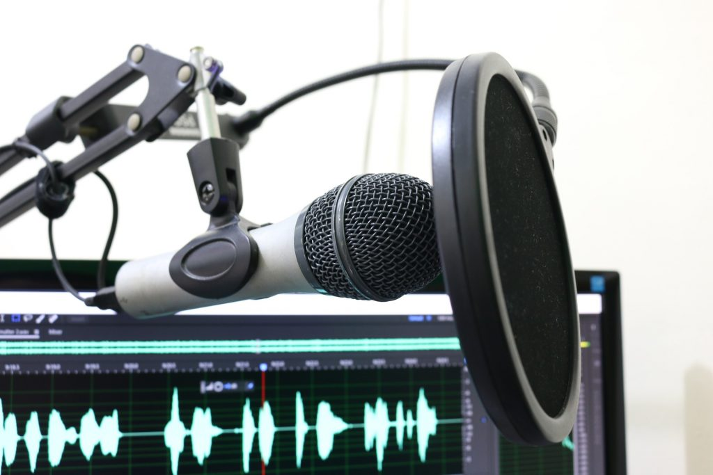 recording microphone with audio software on a computer screen in the background